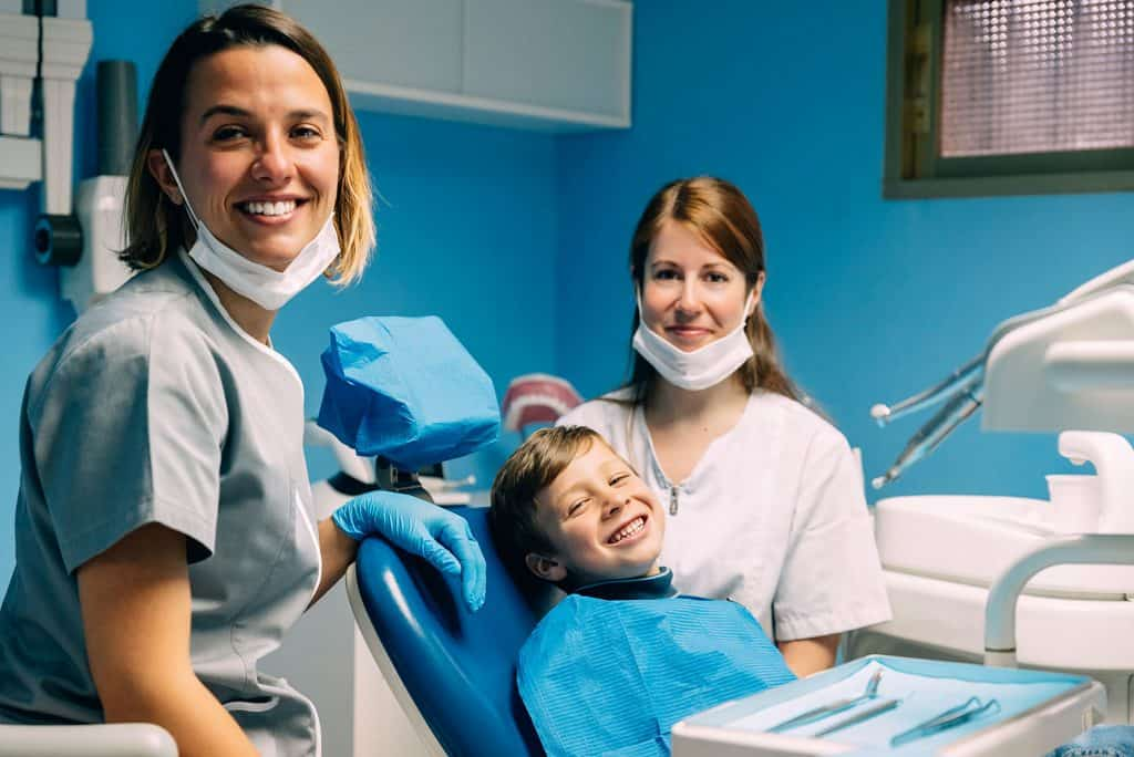 kid smiling with dentists