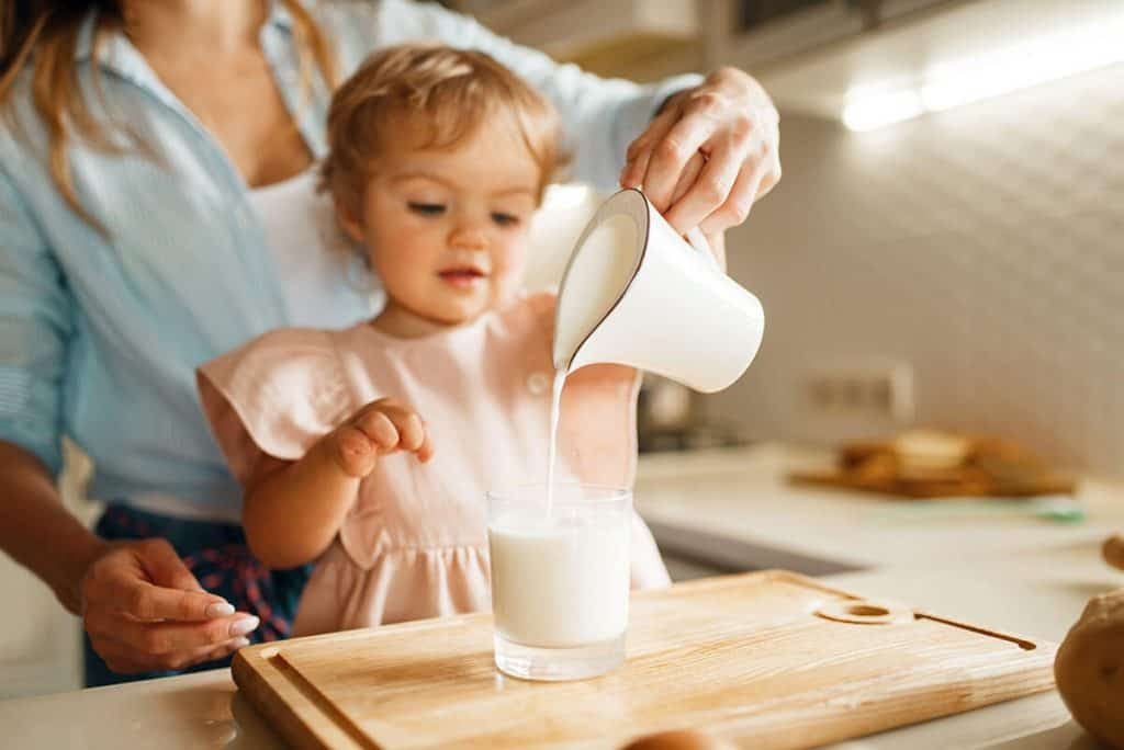 young mother and kid pours milk into a glass