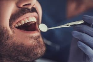 dentist holding a mouth mirror in front of patient's mouth